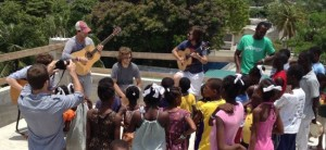 Through their charity, Now I Play Along Too, Melodime plays and teaches music to kids at an orphanage in Haiti.